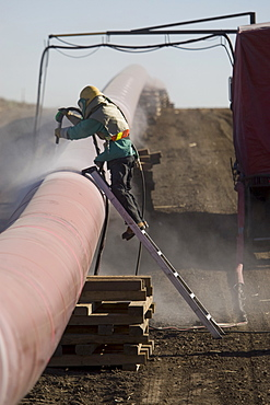 Construction worker cleaning pipeline