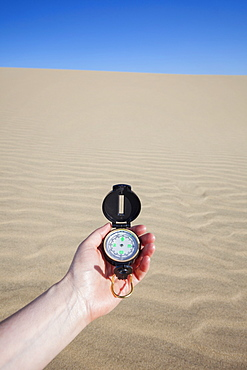 Oregon, Florence, Human hand holding compass with sand dune in background