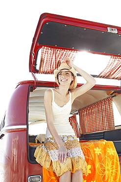 Young woman leaning against back of van