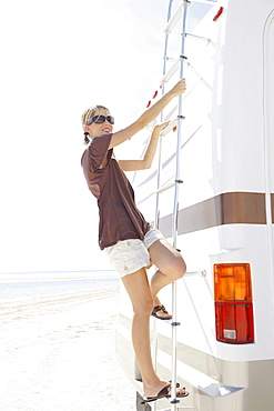 Portrait of woman standing on back ladder of motor home
