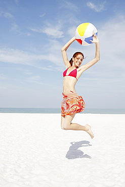 Young woman jumping with beach ball