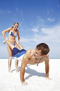 Teenage girl pushing boyfriend on beach