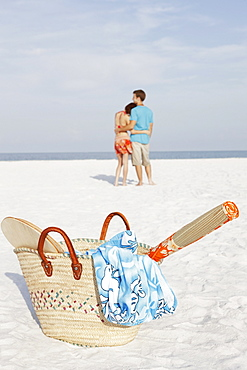 Young couple and beach essentials on beach