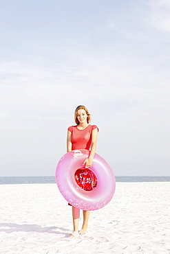 Teenage girl holding inflatable ring on beach