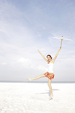 Girl holding umbrella and dancing on beach