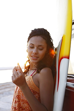 Girl leaning against surfboard on beach