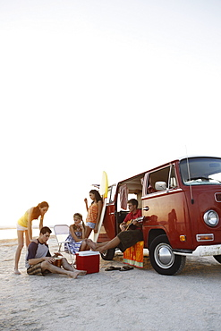 Friends socializing around van on beach