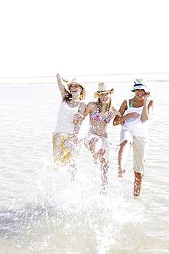 Friends splashing in ocean