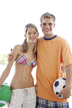 Young couple posing with sports balls