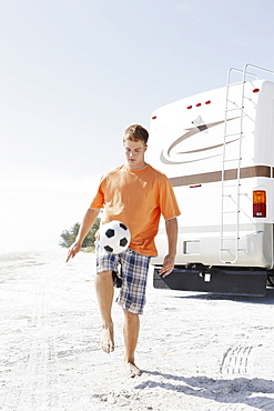 Young man playing with soccer ball on beach