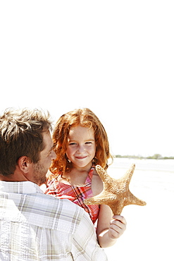 Father carrying daughter and starfish