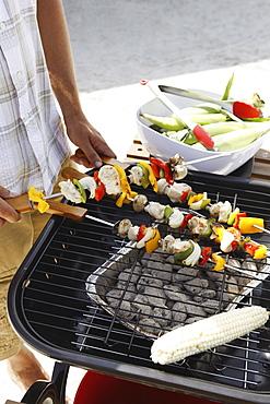 Man grilling shish kebabs and corn