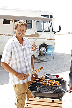 Man grilling shish kebabs on beach