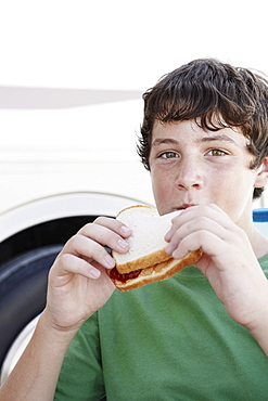 Boy eating peanut butter and jelly sandwich