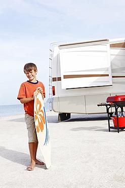 Boy holding skimboard on beach