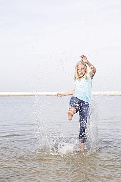Girl kicking water at beach
