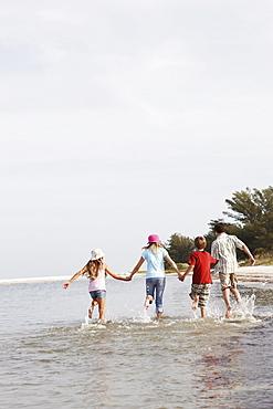 Children running in ocean