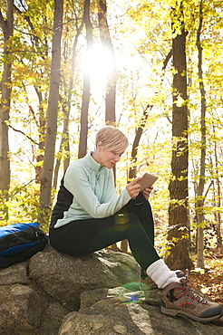 Female hiker using digital tablet in forest