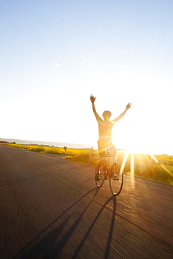 Silhouette of cyclist holding arms up