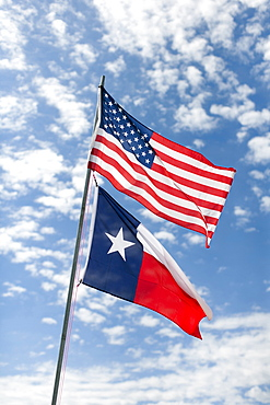 American and Texas flags against cloudy sky, Texas, USA