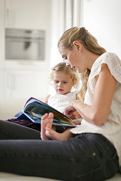 Woman teaching young girl (2-3) at home