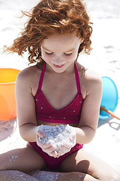 Girl in bikini cupping sand on beach