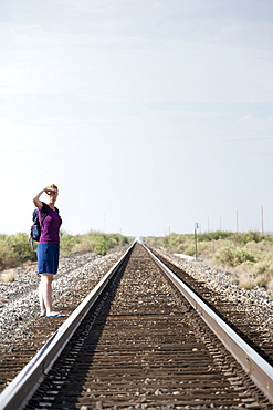 Woman standing by railroad track, Alamogordo New Mexico USA