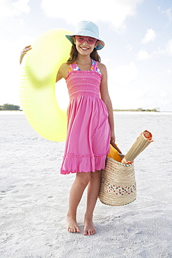 Portrait of girl holding inflatable tube and bag on beach