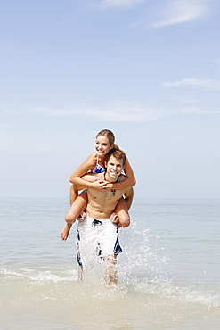 Couple splashing in ocean surf