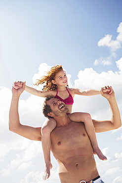 Father carrying daughter in shoulders