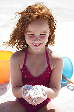 Girl digging in sand on beach