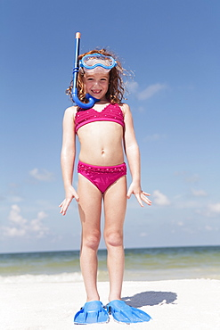Girl on beach wearing snorkeling equipment