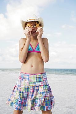 Girl on beach holding starfish