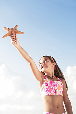 Girl in bathing suit holding up starfish