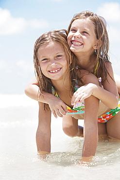 Sisters playing in ocean