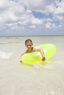 Girl playing in inflatable ring into ocean