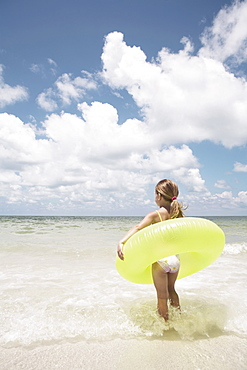 Girl carrying inflatable ring into ocean