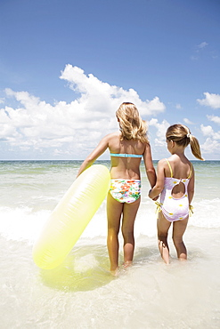 Girls carrying inflatable ring into ocean