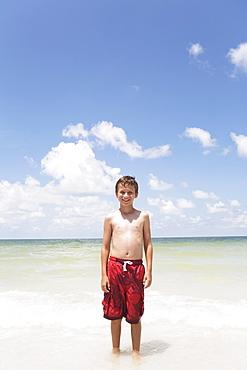 Boy standing in ocean