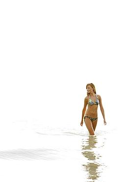 Teenage girl wading in ocean