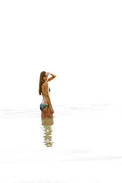 Teenage girl wading in ocean
