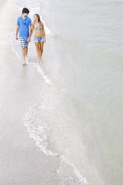Teenage couple walking in ocean