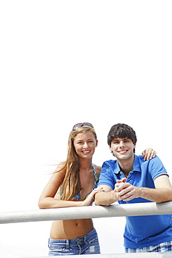 Young couple leaning on boardwalk railing