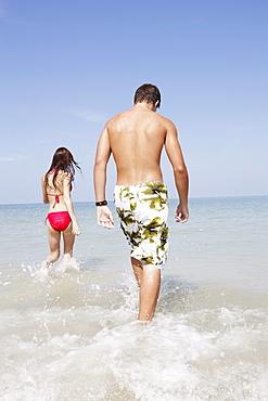 Friends walking in ocean