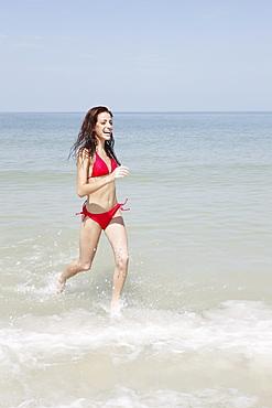 Young woman running in ocean