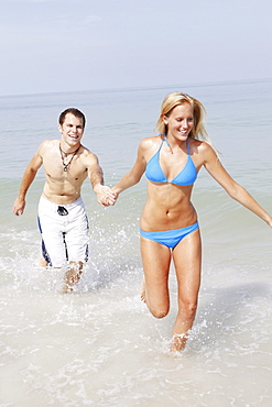 Young couple running in ocean