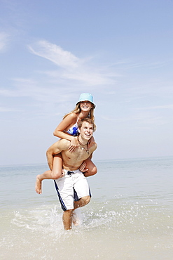 Young man carrying girlfriend on back in ocean