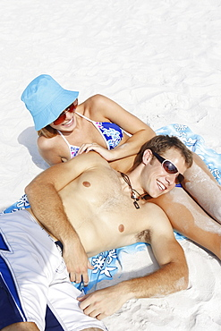 Young couple leisurely sunbathing on beach