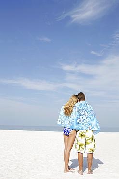 Teenage couple sharing towel on beach