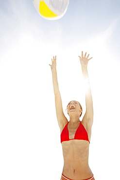 Young woman throwing beach ball in air